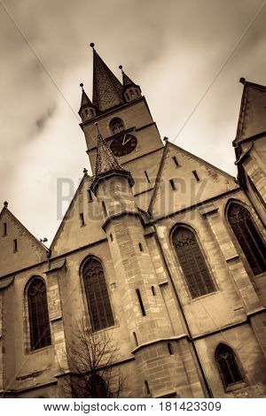 The Lutheran Cathedral in the old medieval city of Sibiu, Romania, under a storm sky. Aged photo look.