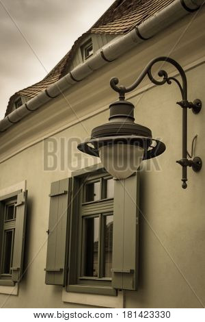 Detail of an old house in the old medieval city of Sibiu with a street lampshade on it. Storm sky. Aged photo look.