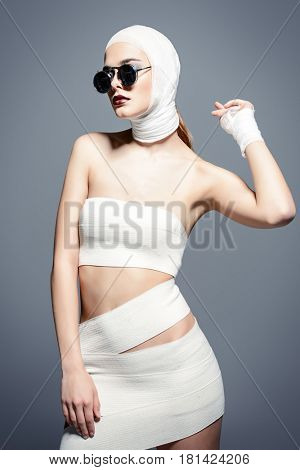 Fashion shot. Attractive young woman in bandages posing at studio. Beauty and medicine, plastic surgery.