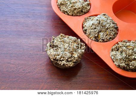 Bread from rye flour with seeds in silicone orange bakeware on table.