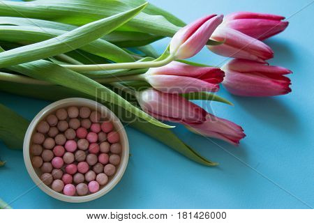 Bouquet of tulips and a cosmetic rouge on a blue background