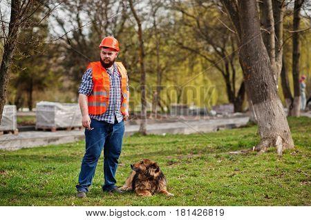 Portrait Of Brutal Beard Worker Man Suit Construction Worker In Safety Orange Helmet With Watchdog.