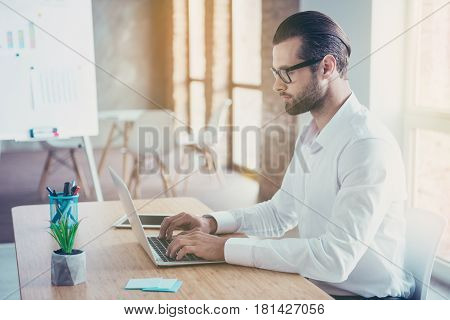 Side View Of Confident Bearded Concentrated Businessman In Glasses And White Shirt Works On Laptop W