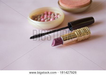 Colorful cosmetic rouge lipstick and mascara on pink background