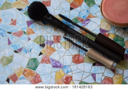 Cosmetic rouge lipstick and mascara on colorful background