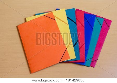 Seven multicolored office folders on wooden desk