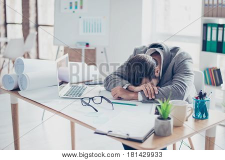 Tired Young Overworked Businessman Is Sleeping At The Table In Modern Lightful Office.