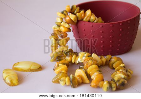 Amber. Beads from amber. Amber necklace on pink background