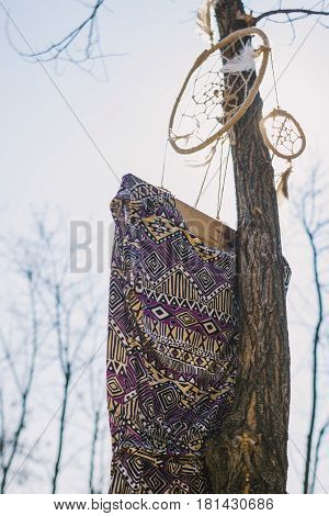 On the tree hanging dream catcher and a woman's dress. hipster style