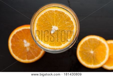 Orange Slice In The Glass, The View From The Top, On A Black Wooden Background, Closeup,