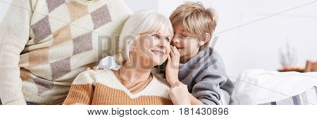 Boy Whispering To Grandma's Ear