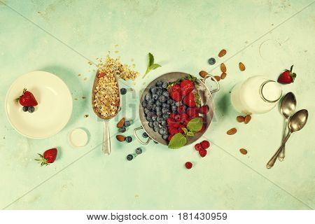 Granola. Breakfast set with granola, almond milk and berries. Healthy eating concept. Copy space background, top view flat lay overhead