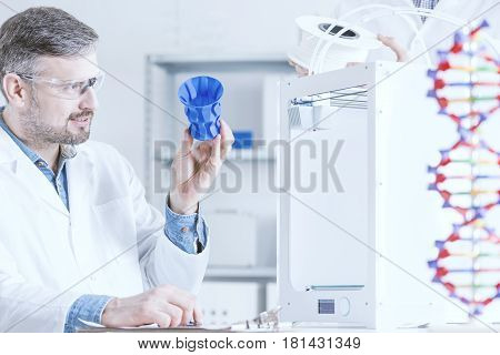 Man Examinig The 3D Printout
