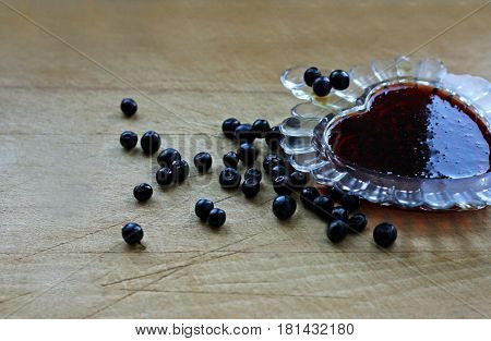 Ripe dark purple berries of a bilberry lying on an old wooden surface. There is a small glass vase with blueberry jam.