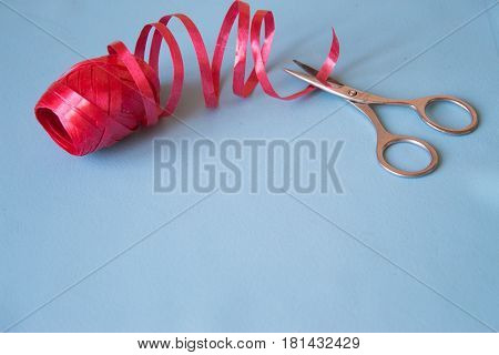 Scissors cut the red ribbon on blue background