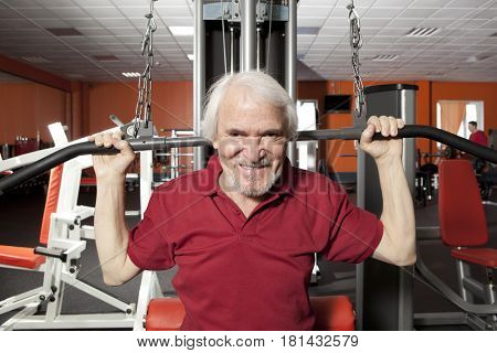 Attractive senior man in gym working out with weights