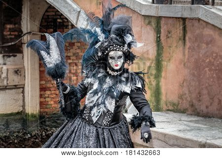 Black carnaval mask with long feathered hat, red lips and delicate tracery standing under the bridge, Venice, Italy.
