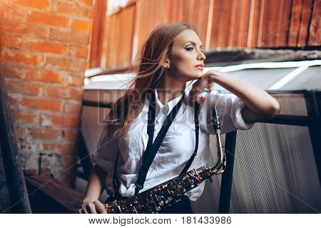 Young attractive girl in white shirt with a saxophone - outdoor in old town. Sexy young woman with sax thinking about something.