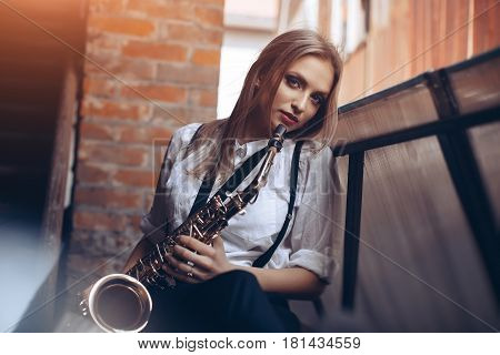 Young attractive girl standing in white shirt with a saxophone - outdoor in old town. Sexy young woman with sax looking at camera.