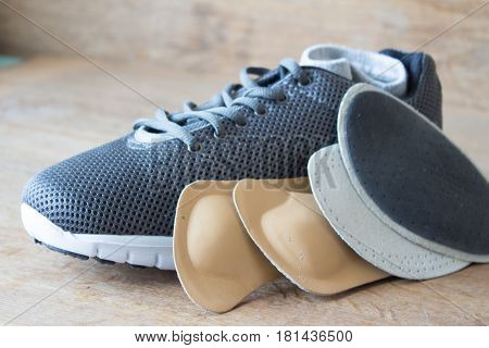 Gray running shoes with orthopedic insoles. Wooden board