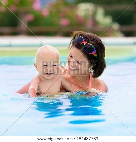 Happy young mother playing with her baby in outdoor swimming pool on hot summer day. Kids learn to swim during family vacation. Children relaxing in tropical resort. Mom and child play in water.