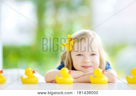 Cute Little Girl Playing With Rubber Ducklings At Home