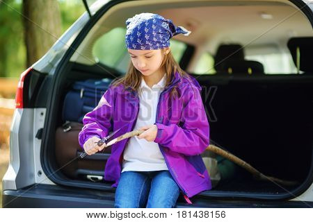 Cute Little Girl Sitting In A Car And Using A Pocket Knife To Whittle A Hiking Stick