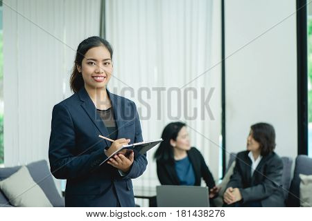Happy young business woman with her staff people group in background at modern bright office indoors.