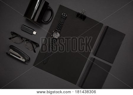 Still life, business, office supplies or education concept : top view image of notepad, mobile phone and coffee cup on black background, ready for adding or mock up