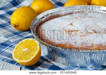 Lemon tart on wooden table and blue napkin
