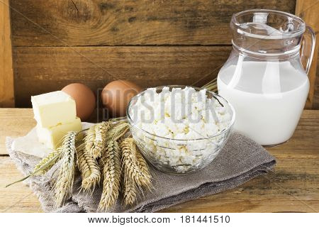 Organic Products: Eggs, Milk, Cottage Cheese, Butter, Wheat On A Wooden Background.