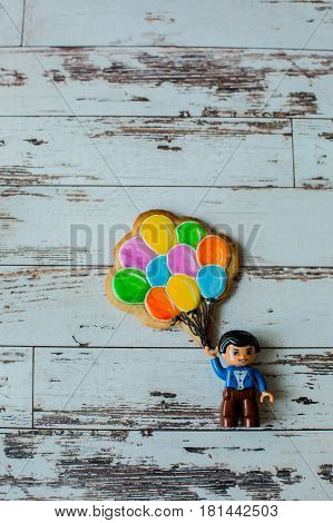 Gingerbread in the form of a tree and balloons with LEGO on a wooden background poster