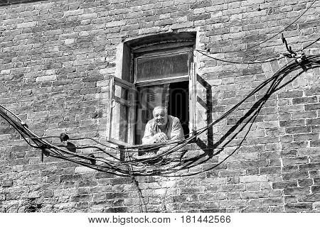 VALAAM, RUSSIA - Aug 15 2015, View of an old man looking out from a window of a brick building, on Aug 15 2015 in VALAAM, RUSSIA