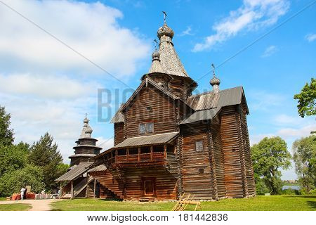 Vintage Russian wooden Church in the village against the blue bright sky. Sunny summer weather.