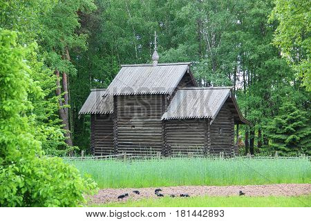 The ancient wooden chapel in village on a green background