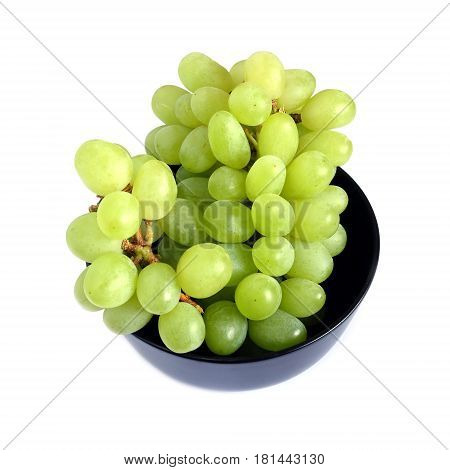 Lot of ripe green grape berries on bunch in black round bowl studio shot on white background top view close up