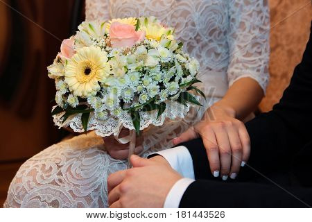 Hands and rings on the background of the costume of the groom and the bride's wedding bouquet
