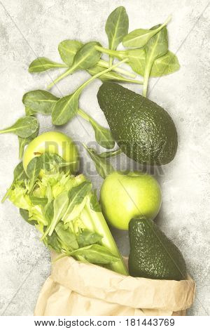 Various Green Vegetables And Fruit - Celery, Apples, Avocado, Spinach In A Paper Package On A Light