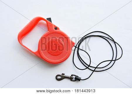 red automatic leash and roll black rope on white background