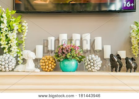 Close up of small table with white unlit candles and flowers part of restaurant interior