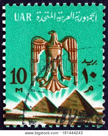 EGYPT - CIRCA 1964: a stamp printed in Egypt shows Eagle of Saladin over Pyramids in Giza circa 1964