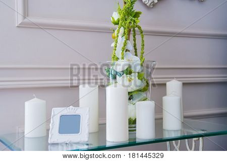 Close up of small table with white unlit candles part of restaurant interior