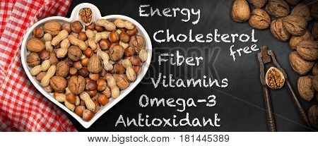 Dried fruits in a bowl in the shape of a heart on a blackboard with text Energy Cholesterol free Fiber Vitamins Omega-3 Antioxidant - Healthy eating