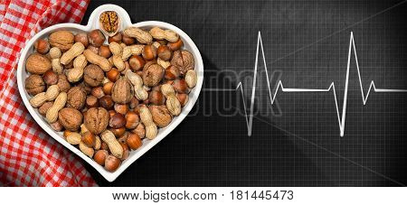 Dried fruits in a bowl in the shape of a heart on a blackboard with a drawing of an electrocardiogram - Concept of healthy food for the heart