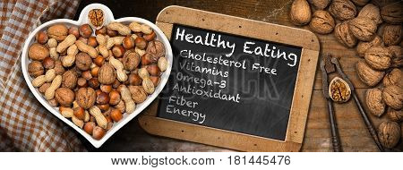 Dried fruits in a bowl in the shape of a heart on a table with a blackboard with chalk texts. Healthy eating cholesterol free vitamins omega-3 antioxidant fiber energy