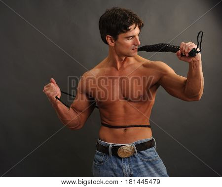 The hot cowboy is holding his lasso.