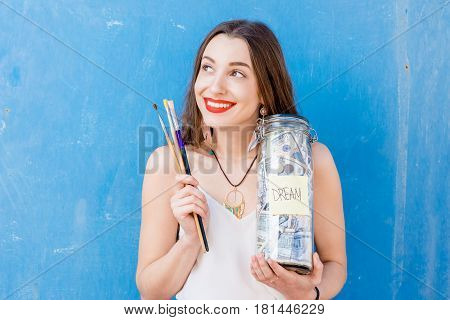 Young woman holding a bottle with money savings for the dream standing on the blue background. Dreaming to be a painter