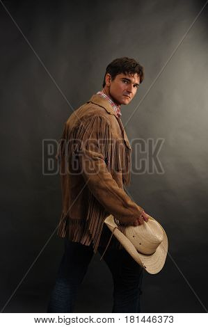 the sexy man is holding a cowboy hat.
