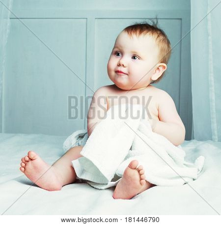 baby at home in bed with a towel after taking a bath