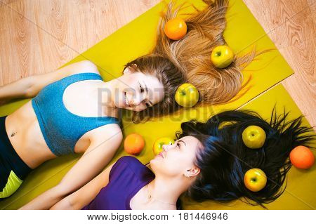 Two Young Athletic Physique Women In Gym Lie On The Floor On Yoga Mats. Fitness Girl With Fruits, Li